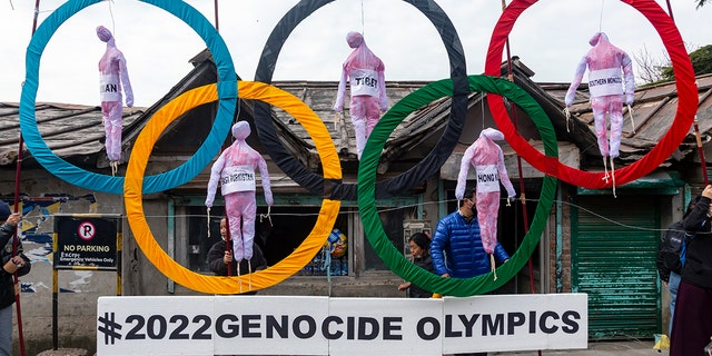 In this Feb. 3, 2021, file photo, exiled Tibetans use the Olympic rings as a prop as they hold a street protest against the holding of 2022 Winter Olympics in Beijing in Dharmsala, India. Some kind of boycott is almost sure to affect next year's Beijing Winter Olympics. (AP Photo/Ashwini Bhatia, File)