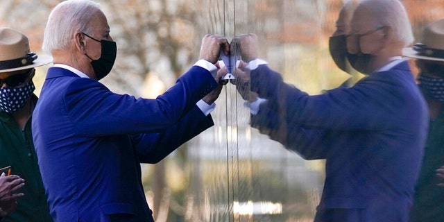 President Joe Biden makes a tracing of Cpl. Dennis F. Shine's name after laying flowers at the Vietnam Veterans Memorial in honor of Vietnam War Veterans Day on Monday, March 29, 2021, in Washington. (AP Photo/Evan Vucci)