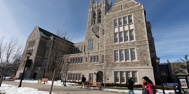 FILE - In this Feb. 17, 2021 file photo, students walk on the Boston College campus in Boston. (AP Photo/Michael Dwyer, File)