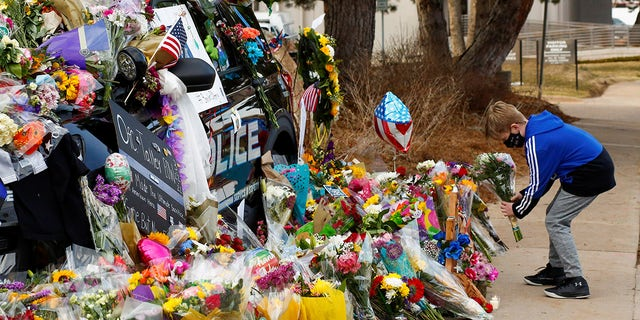 A child lays flowers near the police car of officer Eric Talley who died Monday responding to a call where a gunman opened fire on people in a King Soopers grocery store in Boulder, Colorado, U.S. March 24, 2021.