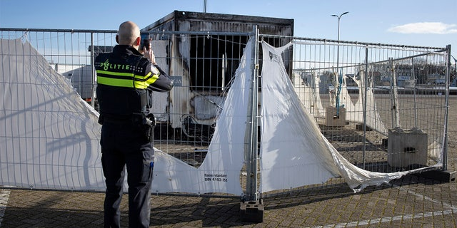 FILE - In this Jan. 24, 2021, file photo, a police officer takes pictures of a burned-out coronavirus testing facility in the fishing village of Urk in the Netherlands after it was set on fire the night before by rioting youths protesting on the first night of a nationwide curfew. (AP Photo/Peter Dejong, File)