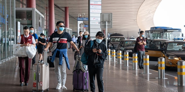 Travelers wearing protective masks push their luggage outside Beijing Capital International Airport in Beijing, China, on Wednesday, Sept. 30, 2020. (Yan Cong/Bloomberg via Getty Images)