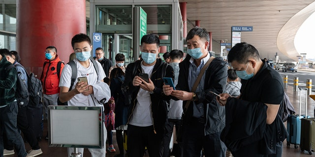 Travelers wearing protective masks use their smartphones to scan a QR code before entering Beijing Capital International Airport in Beijing, China, on Wednesday, Sept. 30, 2020. (Yan Cong/Bloomberg via Getty Images)