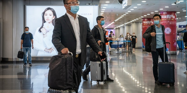 Travelers wearing protective masks push their luggage through Beijing Capital International Airport in Beijing, China, on Wednesday, Sept. 30, 2020. (Yan Cong/Bloomberg via Getty Images)