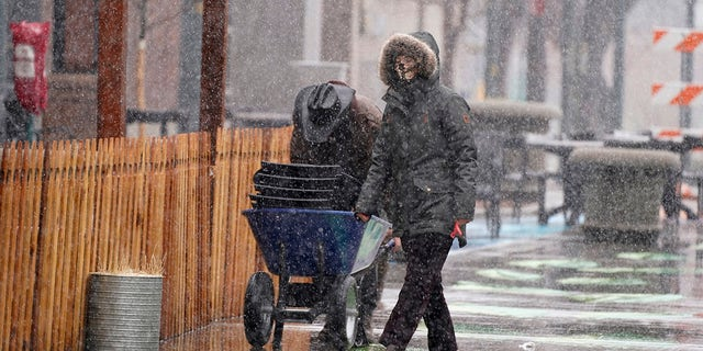 Workers use a wheelbarrell to collect chairs from an outdoor dining area in Larimer Square as a snowstorm sweeps over the intermountain West Saturday, March 13, 2021, in Denver. Forecasters were predicting up to three feet of snow from the lumbering storm, which started slowly around the noon hour Saturday. (AP Photo/David Zalubowski)