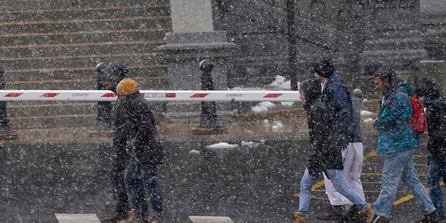 Pedestrians fight blowing snow as they move eastbound along Colfax Avenue as a snowstorm sweeps over the intermountain West Saturday, March 13, 2021, in Denver. (AP Photo/David Zalubowski)