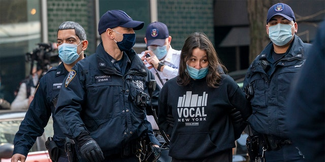 New York Police Officers arrest activists with VOCAL-NY after they blocked traffic on 3rd Ave. outside New York Gov. Andrew Cuomo's office, Wednesday, March 10, 2021, in New York. (AP Photo/Mary Altaffer)