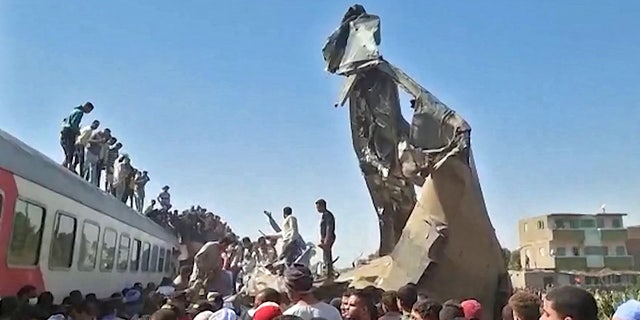 This screengrab provided by AFPTV ahows people gathered around the wreckage of two trains that collided in the Tahta district of Sohag province, some 285 miles south of Cairo, killing at least 32 people and injuring scores of others, on March 26, 2021.