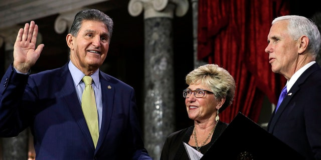US Senator from West Virginia (D) Joe Manchin III is flanked his wife Gayle as he is sworn in by Vice President Mike Pence during the swearing-in re-enactments for recently elected senators in the Old Senate Chamber on Capitol Hill in Washington, DC January 3, 2019. (Photo by Alex EDELMAN / AFP) (Photo credit should read ALEX EDELMAN/AFP via Getty Images)
