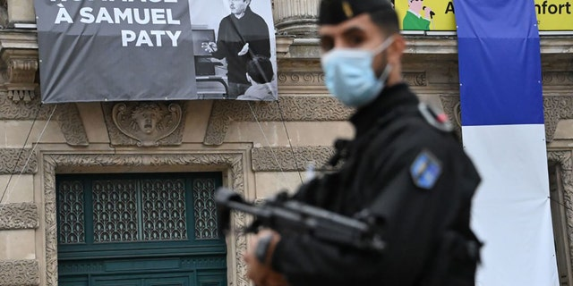 A French police officer stands next to a portrait of French teacher Samuel Paty on display on the facade of the Opera Comedie in Montpellier on October 21, 2020, during a national homage to the teacher who was beheaded for showing cartoons of the Prophet Mohamed in his civics class. (Photo by Pascal GUYOT / AFP) (Photo by PASCAL GUYOT/AFP via Getty Images)