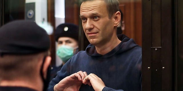 Russian opposition leader Alexei Navalny makes a heart gesture during a hearing into an application by the Russian Federal Penitentiary Service to convert his suspended sentence of three and a half years in the Yves Rocher case into a real jail term on Feb. 2. (Moscow City Court Press OfficeTASS via Getty Images)