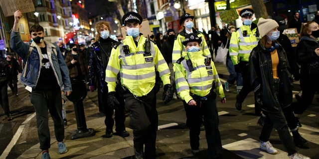 Police officers keep watch as activists protesting violence against women and new proposed police powers demonstrate in London, United Kingdom on March 15, 2021. (Photo by David Cliff/Anadolu Agency via Getty Images)