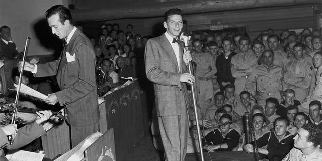 American singer and actor Frank Sinatra performs with Harry James and his orchestra on stage at a concert for American servicemen at the Hollywood Canteen in California.