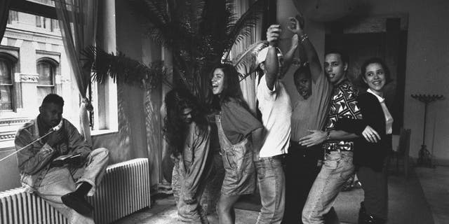 Twentysomething non-actor cast of MTV documentary 'The Real World'. (L-R) Kevin Powell talking on the phone as roomies Andre Comeau, Julie Oliver, Eric Nies, Heather Gardner, Norm Korpi, & Becky Blasband form a conga line in their trendy SoHo loft.