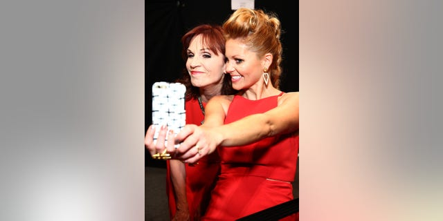 Actresses Marilu Henner and Candace Cameron Bure pose backstage at The American Heart Association's Go Red For Women Red Dress Collection 2016 Presented By Macy's at The Arc, Skylight at Moynihan Station on February 11, 2016, in New York City.