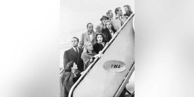 A group of Hollywood stars, representing 500 of their colleagues, leaving Los Angeles for Washington to protest the manner in which Washington's Investigation of Un-American Activities is being conducted. They are left to right, front row: Geraldine Brooks, June Havoc, Marsha Hunt, Lauren Bacall, Richard Conte, and Evelyn Keyes. Left to right, back row: Paul Henreid, Humphrey Bogart, (spokesman for the group), Gene Kelly and Danny Kaye.
