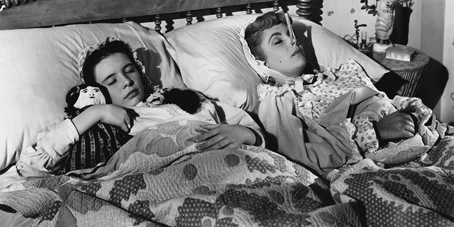 Margaret O'Brien (left) and Elizabeth Taylor forget their troubles in dreams in this scene from MGM's Technicolor production of Louisa May Alcott's 'Little Women'. The clothespin on Taylor's nose is a beauty secret of the time - purported to give the wearer a seemingly slimmer nose. The movie was produced and directed by Mervyn LeRoy.