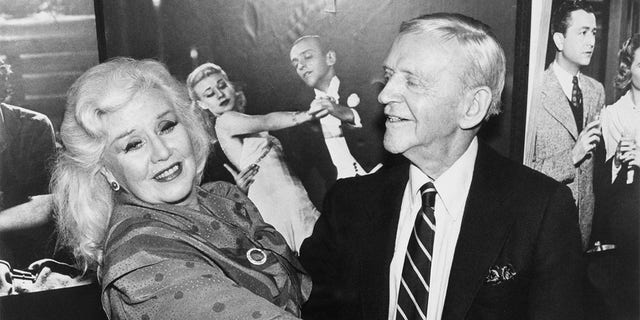 Fred Astaire and Ginger Rogers take a turn around the dance floor June 23 during luncheon celebrating RKO General's donation of RKO Radio Pictures' archives to the University of California, Los Angeles. A poster from one of their films forms the backdrop.