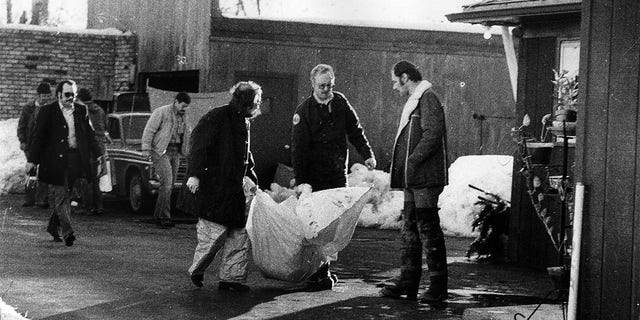 Investigators carry the remains of a body found beneath the garage floor of the home of John Wayne Gacy on December 22, 1978, in Chicago.