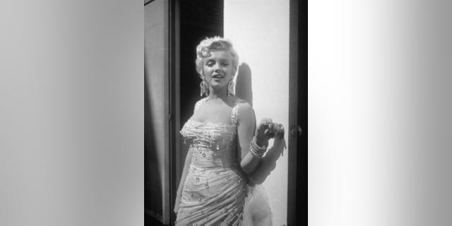 Portrait of Marilyn Monroe in a light-colored, beaded gown, as she leans against an open trailer door on the 20th Century Fox studios set during the filming of director Walter Lang's film, 'There's No Business Like Show Business,' 1954.