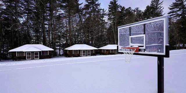 Snow covers a basketball court at Camp Fernwood, a summer camp for girls, Saturday, Feb. 20, 2021, in Poland, Maine. (AP Photo/Robert F. Bukaty)