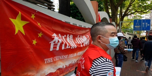A pro-China staff member stands at a stall to support a proposal to draft changes of election rules for Hong Kong on a downtown street in Hong Kong on Friday. (AP)