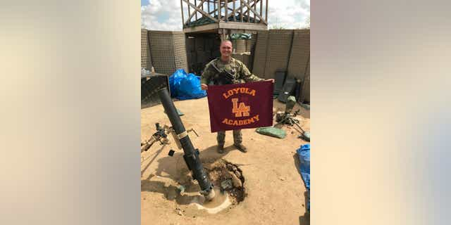 SPC George Kemper holds a Loyola Academy flag while serving in the U.S. Army.