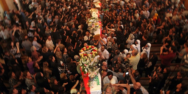 File - In this Tuesday Nov. 2, 2010 file photo, mourners carry the coffins of slain Christians during their funeral in Baghdad, Iraq, who were killed Sunday when gunmen stormed a church during mass and took the entire congregation hostage. (AP Photo/Khalid Mohammed, File)