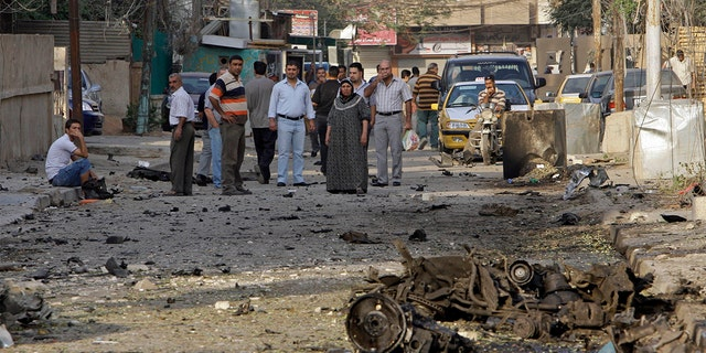 File - In this Monday Nov. 1, 2010 file photo, Iraqis inspect the scene of a car bomb attack in front of a Our Lady of Salvation Church in Baghdad, in Baghdad, Iraq. (AP Photo/Khalid Mohammed, File)