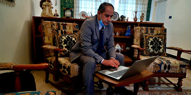 Louis Clemis reviews photos of the storming of the church on his laptop during an interview with The Associated Press in Baghdad, Iraq, Sunday, Feb. 17, 2021. (AP Photo/Hadi Mizban)
