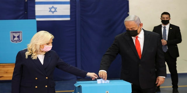 Israeli Prime Minister Benjamin Netanyahu and his wife Sara cast their ballots at a polling station as Israelis vote in a general election in Jerusalem on Tuesday. (AP)