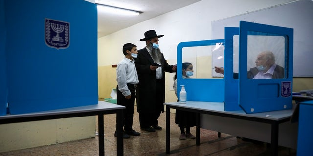An Ultra-Orthodox Jewish man arrives to vote for Israel's parliamentary election at a polling station in Bnei Brak, Israel, on Tuesday. (AP)