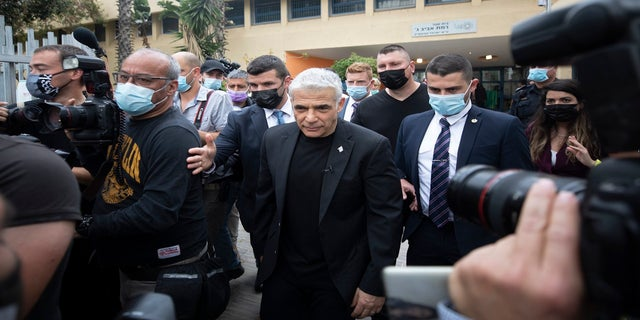 Yesh Atid party leader Yair Lapid leaves after he voted for Israel's parliamentary election at a polling station in Tel Aviv, Israel, on Tuesday. (AP)
