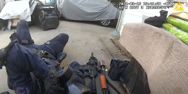 A SWAT officer with the Los Angeles Police Department falls after being shot during a March 16 standoff. The department released police body camera footage of the incident in which a suspected gunman was killed.