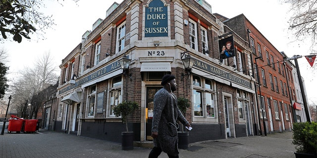 A man walks past the Duke of Sussex pub with a sign depicting the image of Britain's Prince Harry and his wife Meghan, near Waterloo station, London, Tuesday March 9, 2021.  (AP Photo/Frank Augstein)
