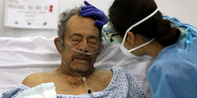 A healthcare worker strokes the forehead of a COVID-19 patient in a field hospital set up inside the Citibanamex convention center in Mexico City, on the first year anniversary that the World Health Organization declared the coronavirus a pandemic. (AP Photo/Fernando Llano, File)