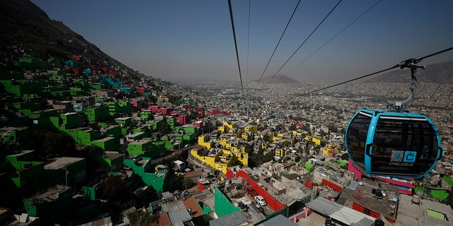Officials and journalists ride in cable cars between the Campos Revolucion and Tlalpexco stations, during the inauguration of a new aerial public transit system dubbed the Cablebus, in the Cuautepec neighborhood of northern Mexico City.