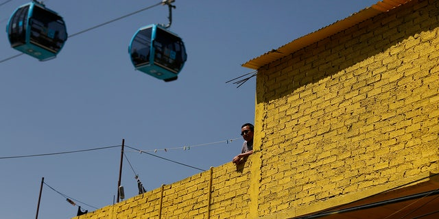 A man stands on a rooftop as cable cars overhead run between the Campos Revolucion and Tlalpexco stations.