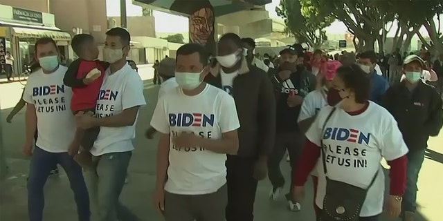 Migrants at the Southern border wear shirts with Biden's campaign logo on them, that say