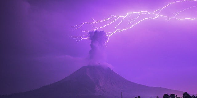 The long-time exposure photo taken on March 5, 2021 shows lightning striking near Mount Sinabung with white smoke being spewed in Karo, North Sumatra, Indonesia. (Photo by Sarianto Sembiring/Xinhua via Getty) ​​​​​