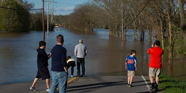 Bellevue residents survey flooding from the Harpeth River on Sunday in Nashville, Tenn. Flash flooding from storms the night before caused road closures in the Bellevue neighborhood. (Reuters)