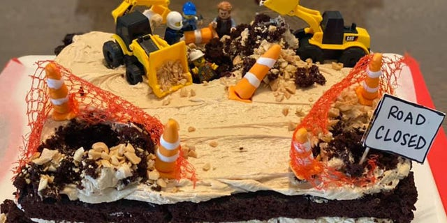 """Inspired, the nurse baked a """"replica"""" cake complete with construction worker Legos, miniature Cat trucks, traffic safety equipment and a """"road closed"""" sign."""