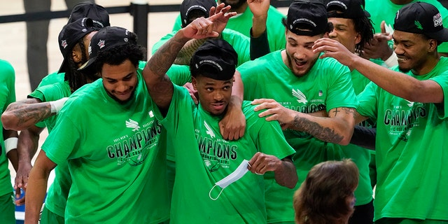 North Texas guard Javion Hamlet, center, celebrates with teammates after the championship game against Western Kentucky in the NCAA Conference USA men's basketball tournament Saturday, March 13, 2021, in Frisco, Texas. North Texas won 61-57 in overtime. (AP Photo/Tony Gutierrez)