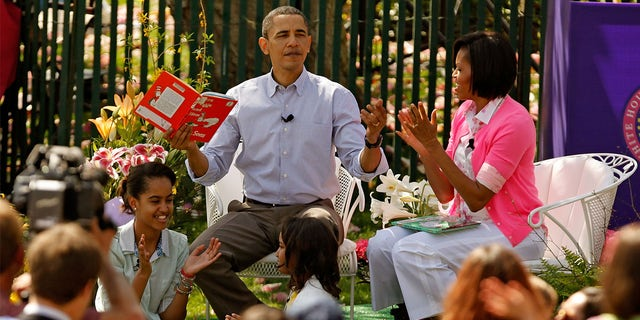 """President And Mrs. Obama Host Easter Egg Roll On White House Lawn WASHINGTON - APRIL 05: U.S. President Barack Obama (C) gets a round of applause after reading """"Green Eggs and Ham,"""" by Dr. Suess, for a group of children and his family, first lady Michelle Obama (R) and daughters Malia Obama (L), 11, and Sasha Obama, 8, during the Easter Egg Roll at the White House April 5, 2010 in Washington, DC. About 30,000 people are expected to attend attended the 132-year-old tradition of rolling colored eggs down the South Lawn of the White House. (Photo by Chip Somodevilla/Getty Images)"""