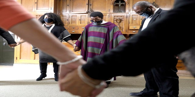 Pastor Thulani Magwaza, center, prays with staff members in the backroom before a Sunday church service at St. Sabina Catholic Church in the Auburn Gresham neighborhood in Chicago, on March 7. (AP)
