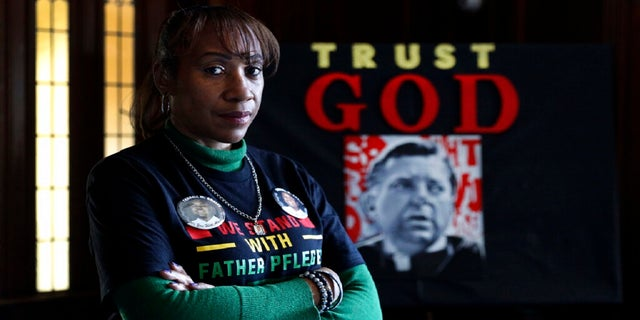 Activist Pam Bosley poses for a portrait infront of a portraiture of Father Michael Pfleger, inside the St. Sabina Catholic Church on March 4. (AP)