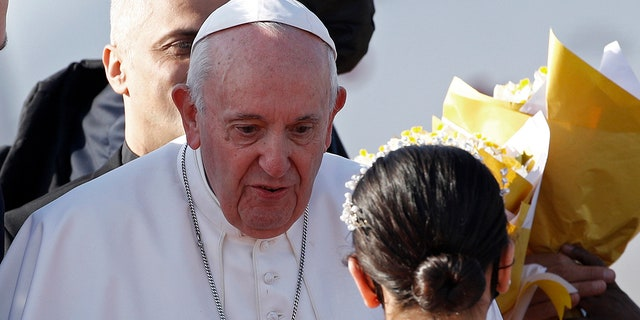 Children give Pope Francis, center, flowers as he arrives at Irbil International Airport, Iraq, Sunday, March 7, 2021. Francis is urging Iraq's long-suffering Christians to forgive the injustices committed against them by Muslim extremists. He asks them to persevere to rebuild the country after years of war and sectarian conflicts. (AP Photo/Hadi Mizban)