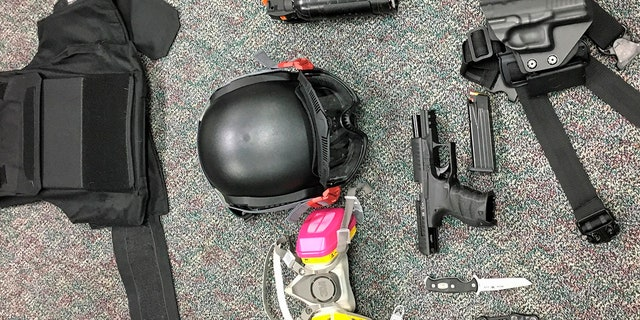 This Friday, March 12, 2021, photo shows numerous items left behind by people inside the perimeter of a march, including a crowbar, hammers, bear spray, slugging weapon with rocks, high impact slingshot, and knives. (Portland Police Department via AP)