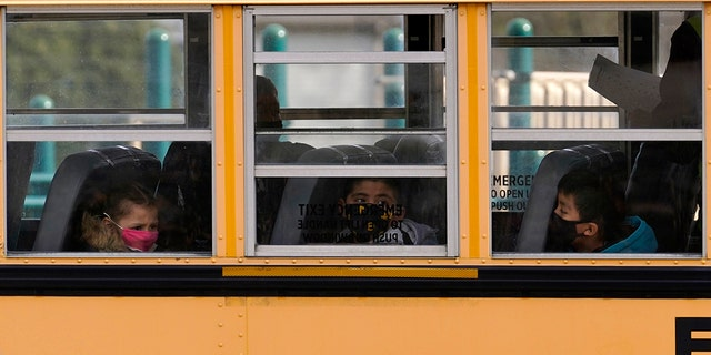 FILE - In this Thursday, Nov. 19, 2020, file photo, elementary school students sit on board a school bus after attending in-person classes at school in Wheeling, Ill. (AP Photo/Nam Y. Huh, File)