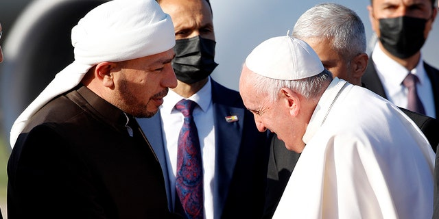 Pope Francis, right, is welcomed by Muslim clerics as he arrives at the Irbil international airport, Iraq, Sunday, March 7, 2021. (Associated Press)